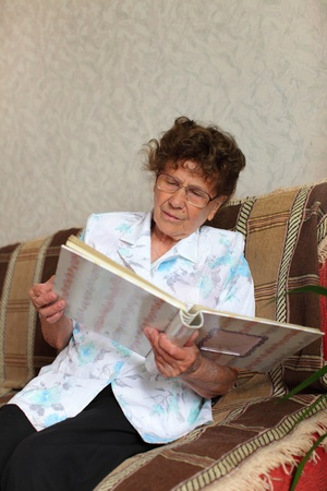 Lonely elderly woman looks a family picture album photo