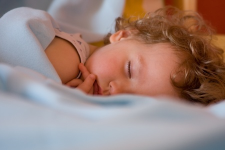 lying on bed: Serenely sleeping a little girl