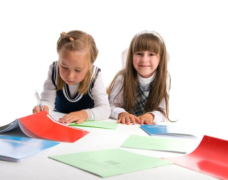 Two schoolgirls with writing-books on a white background photo
