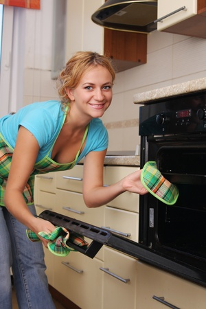 Girl cooks food in an oven photo