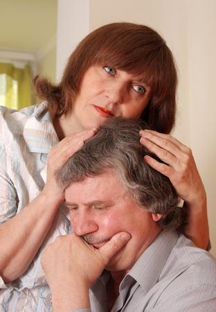 Sad senior couple at home photo