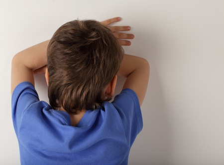 social behaviour: upset boy stands a back Stock Photo