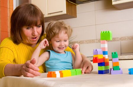 grandchild with grandmother plays cubes at home photo