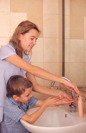 Mum with the son wash hands