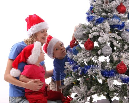 Happy mother and children over christmas tree photo