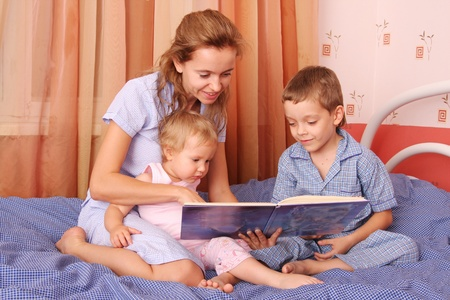 Mum reads the book to the children Stock Photo - 9480834