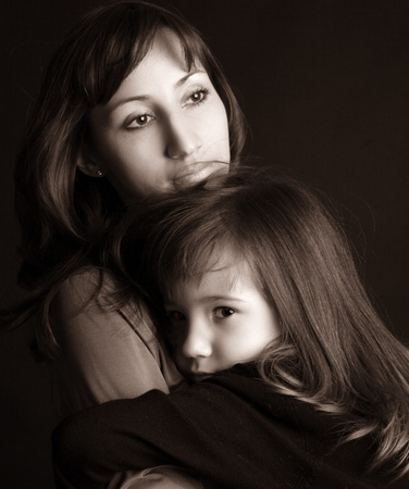consoling: Sad mother and daughter on black