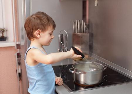 stirring: Little boy cooking porridge in kitchen