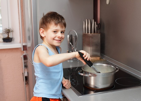 at home accident: Little boy cooking porridge in kitchen