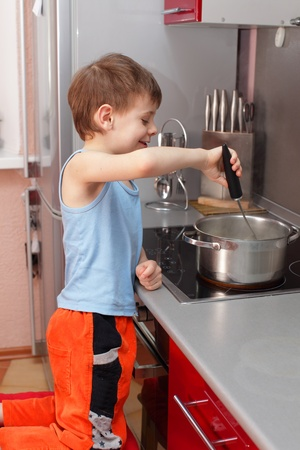 Little boy cooking porridge in kitchen photo