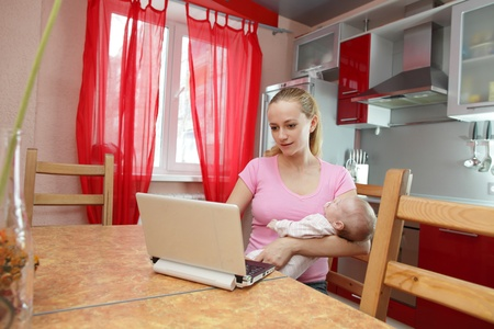 Woman with the laptop and the newborn on kitchen photo