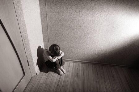 maladroit: Enfant assis dans un coin de la salle