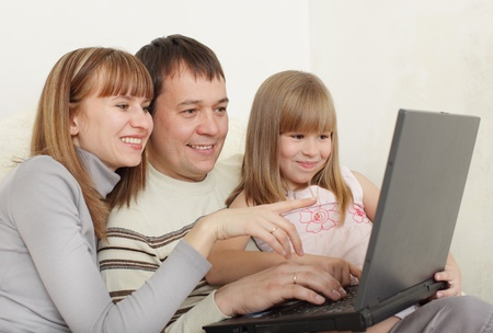 Happy family with laptop at room photo