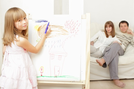 Smiling girl drawing the house photo