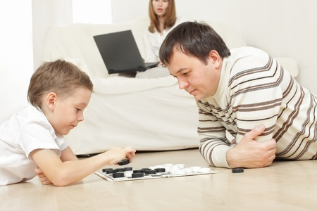 Father with the son playing draughts at home Stock Photo - 9626322