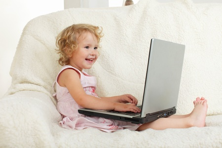 Little girl with laptop at home photo