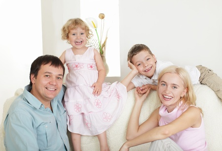 Happy family with two children on sofa Stock Photo - 9626474