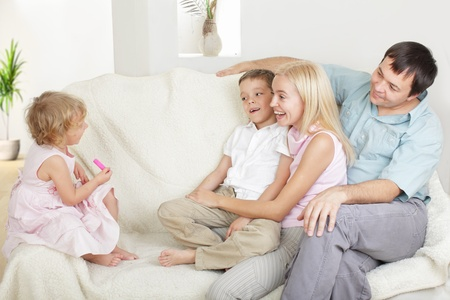 Happy family with two children on sofa Stock Photo - 9626493