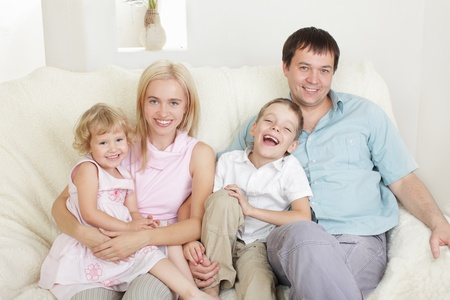 Happy family with two children on sofa Stock Photo - 9626487