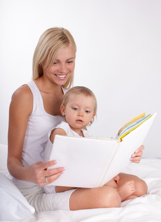 Mother reading book to a daughter at home photo