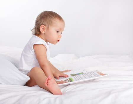 Baby reading book on the bed photo
