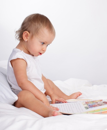 Baby reading book on the bed Stock Photo - 10232360