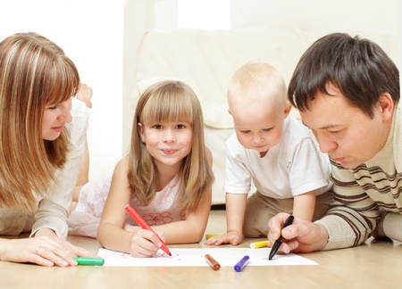 Parents with children drawing laying on a floor photo