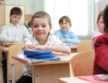 Schoolchild behind desks at school Stock Photo - 10998403