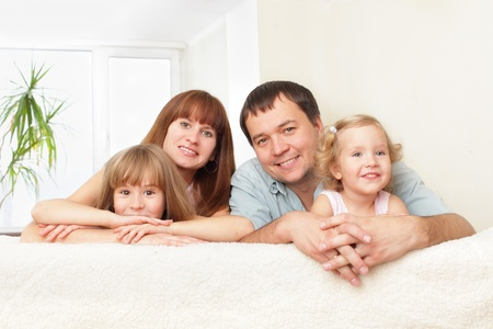 Happy family with two children on sofa photo