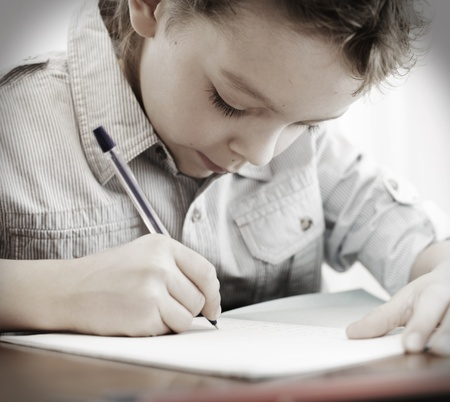 children writing: Little boy does a homework