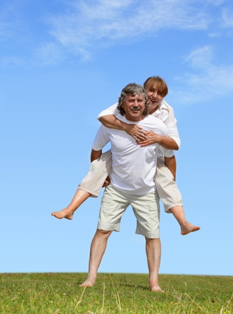 affectionate actions: Happy mature pair against the sky