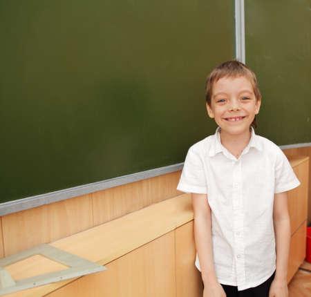 school age boy: Happy schoolboy before a board