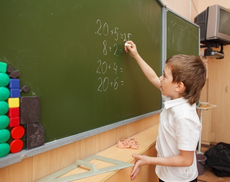 teaching and learning: Schoolboy about a board solves examples Stock Photo