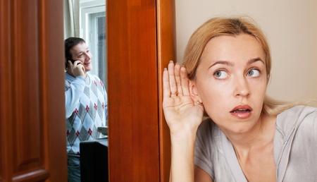 La celosa esposa, al oír una conversación telefónica a su esposo Foto de archivo
