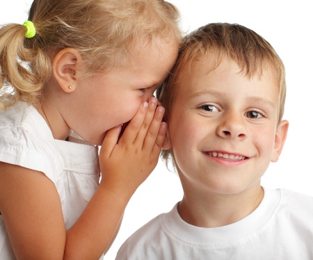 children talking: Girl whispers a secret to the boy