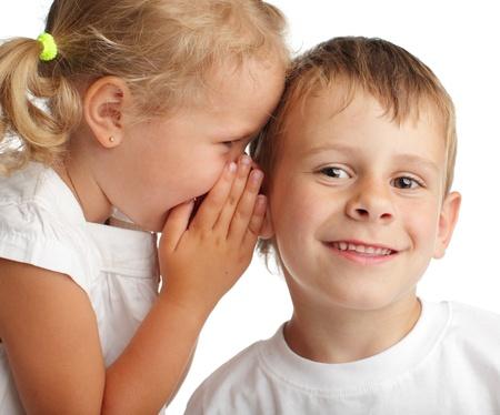 children talking: Girl whispers a secret to the boy