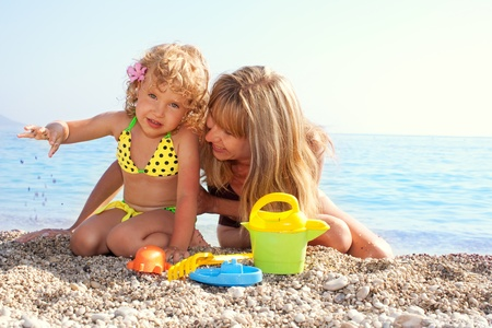 beach toys: Beautiful little girl with mother on the beach