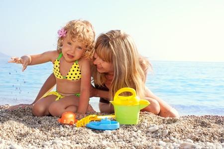 klein meisje op strand: Mooi meisje met moeder op het strand