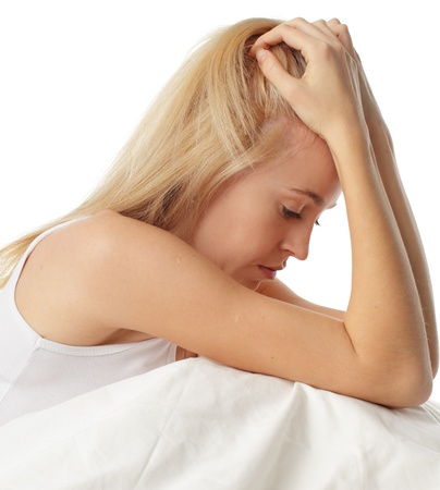 worried: Worried young woman on bed