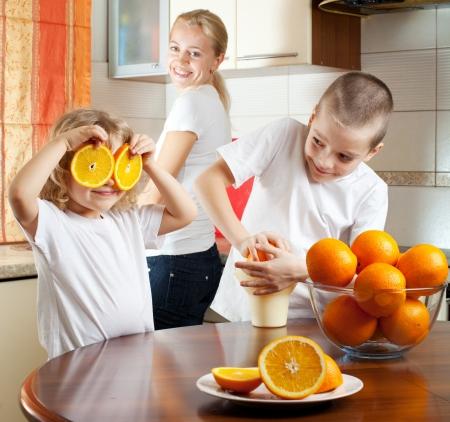 squeezed: Felice madre con i bambini succo d'arancia Archivio Fotografico