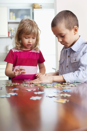 Children, playing puzzles at home photo