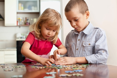 2 persons only: Children, playing puzzles at home Stock Photo