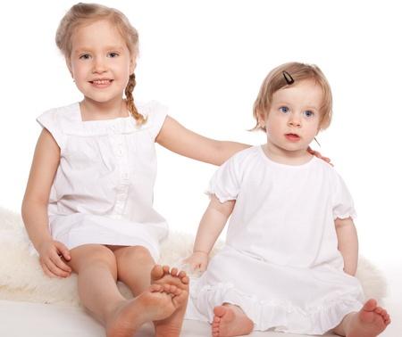 Kleines Mädchen mit schönen Baby auf weißem Hintergrund