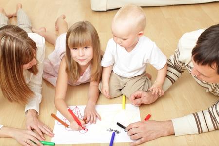 적층: 아이들과 부모는 바닥에 누워 그리기 스톡 사진