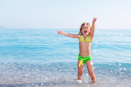 little girl beach: Happy little girl playing on the beach Stock Photo