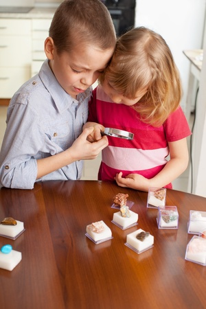 Children playing with a magnifying glass, looking at a collection of stones photo