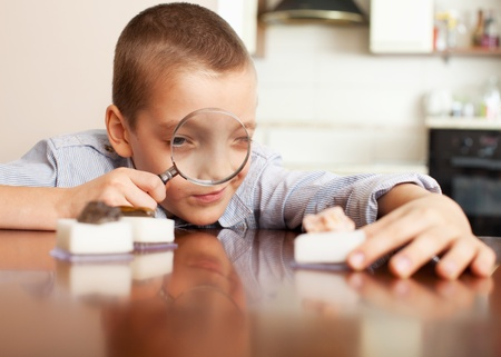 archaeology: Young boy playing with a magnifying glass looking at a collection of stones Stock Photo