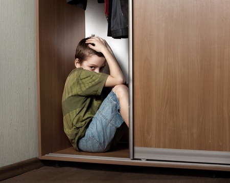 frighten: Sad boy, hiding in the closet at home
