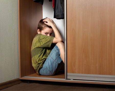boy crying: Sad boy, hiding in the closet at home