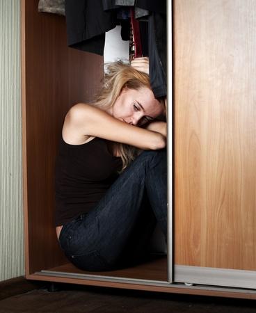 woe: Sad woman sitting in the closet Stock Photo